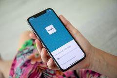 Рука женщины держа iPhone x с такси Uber применения стоковые фото