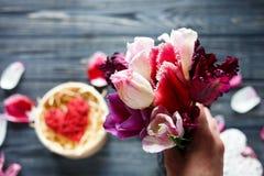 Рука женщины держит букет тюльпанов цветков и красное деревянное сердце лежит в коробке на темной таблице с пинком, фиолетовых ле стоковые изображения