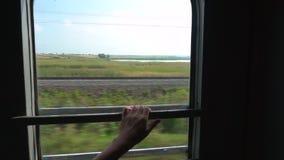 Рука женщины держит поручень на окне поезда сток-видео