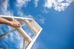 Рука женщины достигая для красной лестницы водя к голубому небу стоковое фото rf