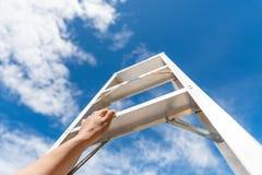 Рука женщины достигая для красной лестницы водя к шагу голубого неба стоковое фото rf