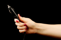 Рука женщины держа автоматический соединитель лихтера сигареты на черной предпосылке Стоковые Изображения RF