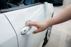 Рука женщины держа автомобиль двери для того чтобы открыть или зафиксировать Стоковая Фотография RF