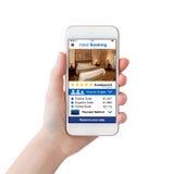 Рука женщины держа белый телефон с экраном бронирования гостиниц app