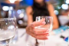 Рука женщины держа бокал на ресторане стоковая фотография