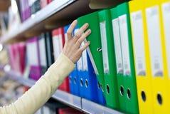 Рука девушки принимая большой скоросшиватель от полок с офисом хранит. Стоковое Изображение RF