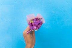 Рука женщины держа букет розовых цветков Стоковое Изображение
