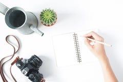Рука женщины держа карандаш на пустой тетради с камерой фильма, Стоковое Изображение RF
