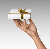 Рука женщины держа коробку праздника присутствующую белую с оранжевой золотой лентой Стоковые Изображения RF