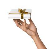 Рука женщины держа коробку праздника присутствующую белую с оранжевой золотой лентой Стоковая Фотография