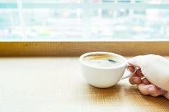 Рука женщины держа кофейную чашку эспрессо на деревянной таблице в острословии кафа Стоковое Изображение
