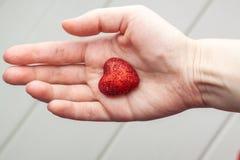 Рука женщины держа малое пластичное сердце Стоковое Изображение RF