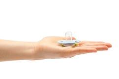 Рука женщины держа ниппель куклы ребенк Стоковая Фотография