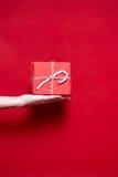 Рука женщины держа подарок коробки с леденцом на палочке рождества на красном ба Стоковые Изображения