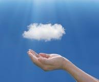 Рука женщины держа под облаком на голубой предпосылке, comput облака стоковые изображения