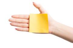 Рука женщины держа пустой желтый notepaper Стоковые Изображения RF