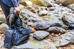 Рука женщины держа рюкзак, шляпу и сандалии готовыми идти через поток воды стоковые фотографии rf