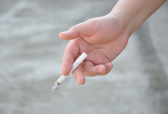 Рука женщины держа сигарету Стоковые Изображения