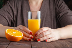 Рука женщины держа стекло апельсинового сока Стоковые Фото