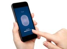 Рука женщины держа телефон и входя в код PIN пальца Стоковая Фотография