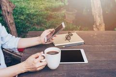 Рука женщины держа телефон и используя телефон на таблице в саде стоковое изображение