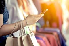 Рука женщины держа хозяйственные сумки и используя smartphone Стоковые Изображения