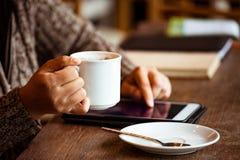 Рука женщины держа чашку кофе и используя цифровую таблетку Стоковые Фото