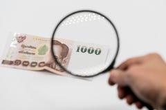 Рука женщины держа черное стекло увеличителя проверяя тайские деньги Стоковые Изображения RF