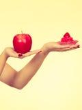 Рука женщины держа яблоко и пирожное помадки Стоковые Изображения