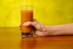 Рука женщины держит сок персика в стекле Стоковое фото RF