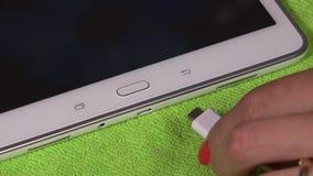 Рука женщины затыкая белый кабель usb micro к умному планшету сток-видео