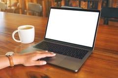 Рука женщины использующ и касающся на сенсорной панели ноутбука с экраном пробела белым настольным с кофейной чашкой на деревянно стоковые изображения