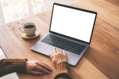 Рука женщины использующ и касающся на сенсорной панели ноутбука с экраном пробела белым настольным с кофейной чашкой на деревянно стоковое фото