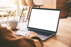 Рука женщины использующ и касающся на сенсорной панели ноутбука с экраном пробела белым настольным с кофейной чашкой на деревянно стоковые фото