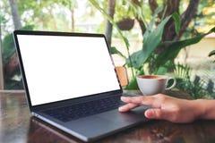 Рука женщины использующ и касающся на сенсорной панели ноутбука с экраном пробела белым настольным с кофейной чашкой на деревянно стоковое фото rf