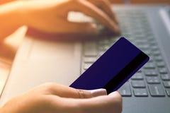 Рука женщины используя кредитную карточку и печатать на тетради компьютера для ходить по магазинам онлайн Стоковые Фото