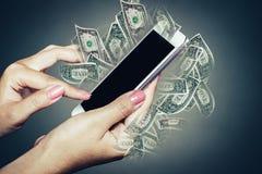 Рука женщины используя мобильный телефон технологии с банкнотами в предпосылке Стоковое Изображение