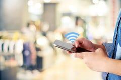 Рука женщины используя умный значок телефона и wifi над магазином нерезкости с Стоковые Изображения