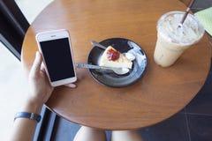 Рука женщины используя умный телефон в кофейне Стоковое фото RF