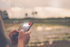 Рука женщины используя smartphone для посылки и для того чтобы получить электронной почты стоковое фото