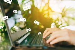 Рука женщины используя smartphone для посылки и для того чтобы получить электронной почты для дела стоковые изображения