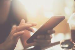Рука женщины используя smartphone или таблетку для того чтобы сделать дело стоковая фотография
