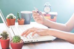 Рука женщины используя портативный компьютер и кредитную карточку держать Стоковая Фотография