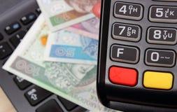 Рука женщины используя стержень оплаты, польские деньги валюты на компьтер-книжке Стоковая Фотография