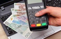 Рука женщины используя стержень оплаты, польские деньги валюты на компьтер-книжке Стоковое Изображение