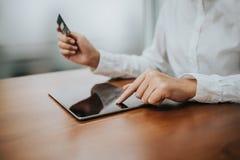 Рука женщины используя таблетку и кредитную карточку Стоковое Изображение