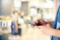 Рука женщины используя умный телефон над магазином нерезкости с backgrou bokeh Стоковая Фотография