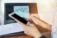 Рука женщины используя умный телефон пока анализировать финансовый и диаграмма запаса на ее тетради Стоковое фото RF