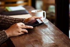 Рука женщины используя цифровую таблетку в кафе в дождливом дне Стоковая Фотография
