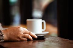 Рука женщины используя цифровую таблетку в кафе в дождливом дне Стоковое фото RF